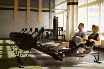 Man and woman training on rowing machines in gym together
