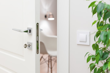 Close-up elements of the interior of the apartment. Ajar white door. Chrome door handle and lock with key