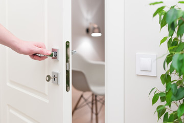 To open the door. Modern white door with chrome metal handle and a man's arm