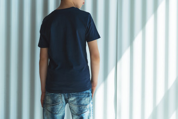 Back view. Young hipster boy dressed in black t-shirt is stands indoor against white wall. Mock up. Space for logo, text, image.
