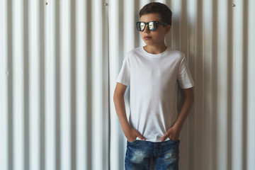 Front view. Young hipster boy in sunglasses dressed in white t-shirt is stands indoor against white wall. Mock up. Space for logo, text, image.