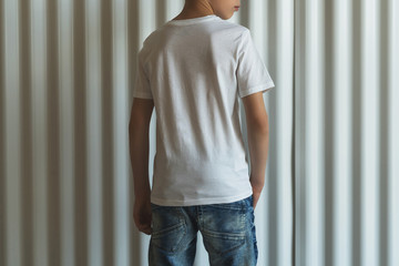 Back view. Young hipster boy dressed in white t-shirt is stands indoor against white wall. Mock up. Space for logo, text, image.