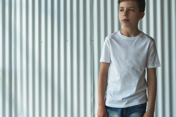 Front view. Young hipster boy dressed in white t-shirt is stands indoor against white wall. Mock up. Space for logo, text, image.