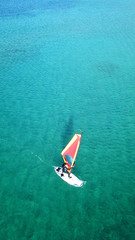 Aerial drone bird's eye view of man surfing in paradise tropical turquoise clear waters