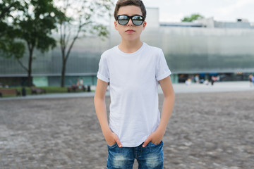 Front view. Young hipster boy in sunglasses dressed in white t-shirt is stands outdoor. Mock up. Space for logo, text, image.