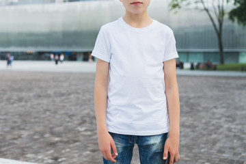 Summer day. Young hipster boy dressed in white t-shirt is stands outdoor. Mock up. Space for logo, text, image.