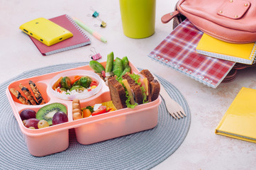 Lunch box with sandwiches, vegetable salad, fresh fruits and nuts on the table near school backpack