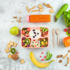 Lunch box with vegetable salad, berries in yougurt, fruits and rice on grey background with ingredients