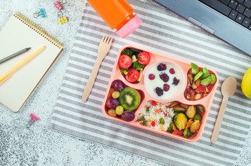 Lunch box with vegetable salad, berries in yougurt, fruits and rice on office table
