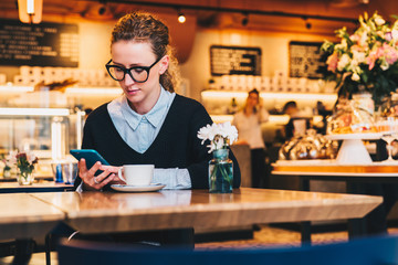 Young business woman in glasses sits in cafe at table, uses smartphone. On table is cup of coffee. Girl working, chatting, blogging, checking email. Online marketing, education, social media, network.