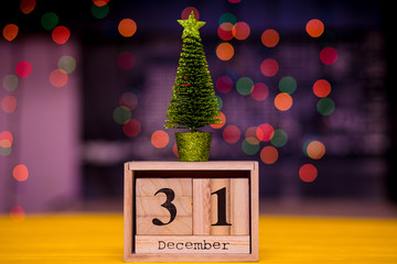 December 31st. Day 31 of December set on wooden calendar on blurred garland bokeh background with a Christmas tree. Winter time. New year background. Christmas Holiday Composition