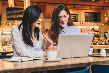 Two young businesswomen,bloggers, wearing in shirts are sitting in cafe at table and using laptop, working, studying.Girls look at monitor in amazement,delightedly,joyfully.Online marketing,education.