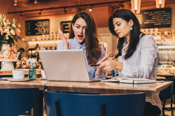 Two young businesswomen, bloggers are sitting in cafe at table and using laptop.Girl showing pen on computer screen,girls look at monitor in amazement, delightedly, joyfully.Online shopping, blogging.