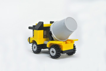 Small model of Construction Mixer Lorry made of plastic bricks isolated on white background.