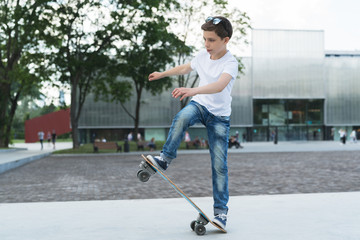 Summer day. The boy is a teenager dressed in a white T-shirt and jeans, skating, doing tricks. In the background is a modern glass building. Vacation, recreation, entertainment, activity.