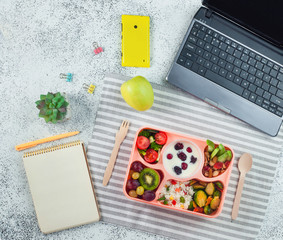 Open lunch box with healthy lunch with empty notebook on grey background