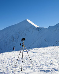 Tripod for photography with camera, ski poles on snow and snow-capped mountains