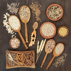 High fibre health food of whole wheat pasta, cereal and grains in bowls and spoons on rustic oak background.