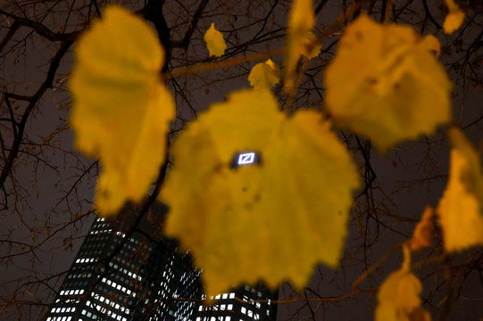 The logo of Germany's largest business bank, Deutsche Bank, is photographed through a dead leaf at the bank's head quarters in Frankfurt