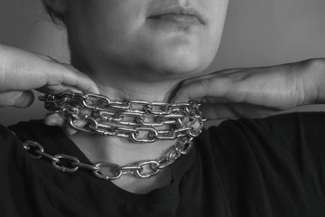 Photo of hands releasing the neck from a metal chain