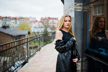 Blonde fashionable girl in long black leather coat posed against large window of building.