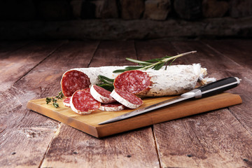 Marble cutting board with sliced salami on it