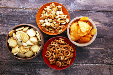 Salty snacks. Pretzels, chips, crackers in wooden bowls