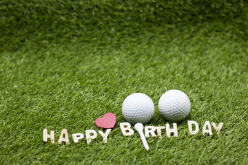 Happy birthday to golfer lettering on green grass with golf balls and tee