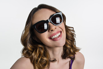 Young brunette in sunglasses looks at camera and smiles.