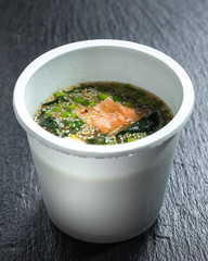 Miso salmon soup over slate plate background in take-out container