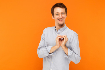Love concept. Happiness young adult man showing shape heart at camera and toothy smile