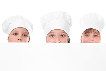 Cute children in chef's hats holding blank poster on white background