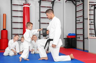 Male karate instructor training little boy in dojo