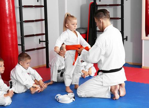 Male karate instructor with little children in dojo