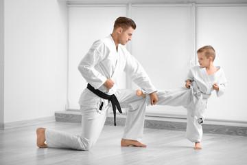 Little boy with instructor practicing karate in dojo