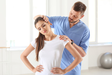 Physiotherapist working with young female patient in clinic