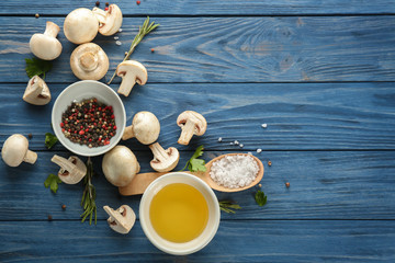 Fresh champignon mushrooms with spices on wooden background