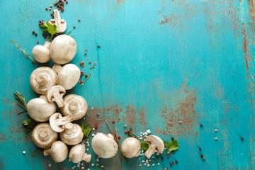 Fresh champignon mushrooms on wooden background