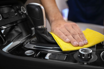 Man cleaning car gear lever with rag, closeup