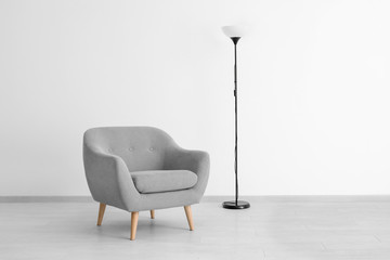 Comfortable armchair and lamp near light wall