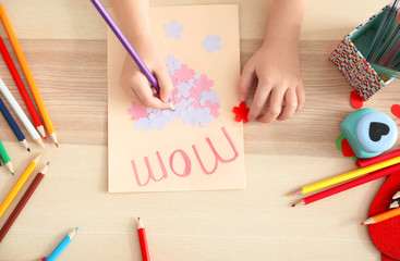 Little girl drawing greeting card for Mother's day at table