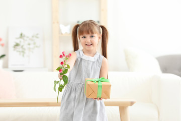Little girl holding gift box and flower for Mother's day at home