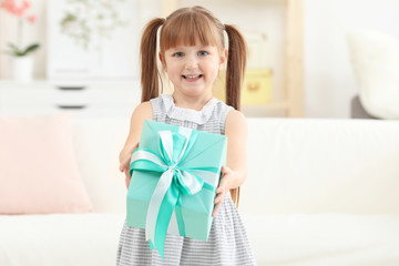 Little girl holding gift box for Mother's day at home