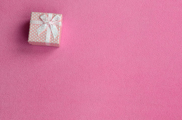 A small gift box in pink with a small bow lies on a blanket of soft and furry light pink fleece fabric. Packing for a gift to your lovely girlfriend