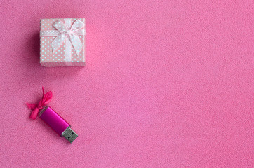 Brilliant pink usb memory card with a pink bow lies next to a small gift box in pink with a small bow on a blanket of soft and furry light pink fleece fabric. Classic female gift memory card design