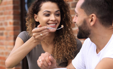 Young couple enjoying coffee at a street cafe and  laughing