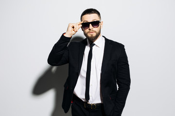 Portrait of a concentrated handsome man dressed in suit and hands on sunglasses looking away while standing over gray background