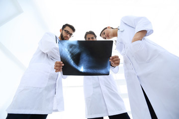 three doctors studying the patient's X-ray film