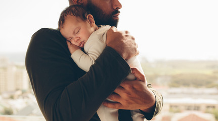 Newborn baby boy in his father's arms