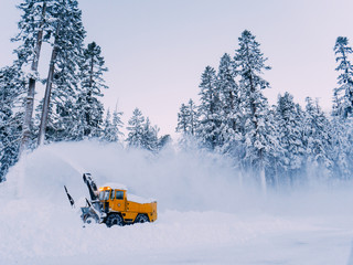 Tractor is best for snow plowing (snow removal). California winter, Mammoth ski resort. Plowing deep snow